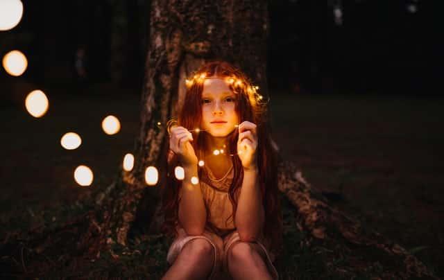 Garotinha sentada com fio de luzes nas mãos e em volta da cabeça