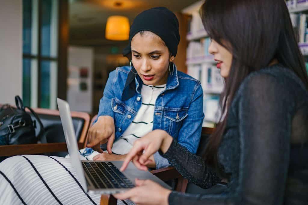 Duas mulheres conversando e olhando um computador.