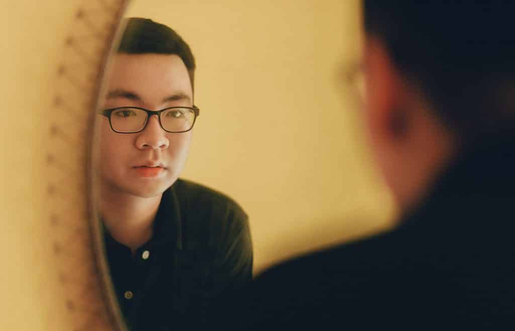 Homem com expressão séria olhando para o seu reflexo no espelho.