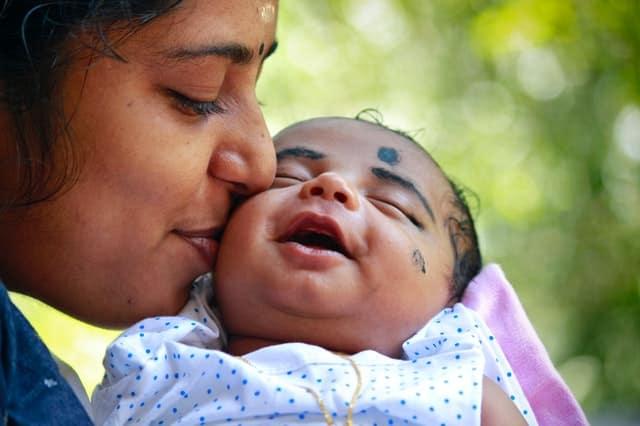 Mãe beijando rosto de filha bebê que está sorrindo