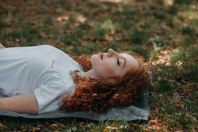 Mulher deitada em toalha na grama de olhos fechados