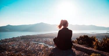 Mulher sentada em uma rocha olhando para o horizonte