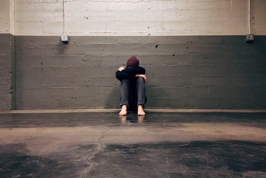 Pessoa branca sentada no chão com pernas e braços encolhidos e cabeça baixa.