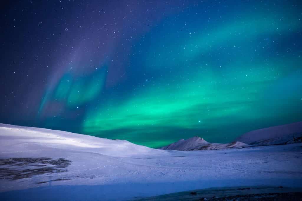 Foto de uma aurora boreal em uma montanha com neve.