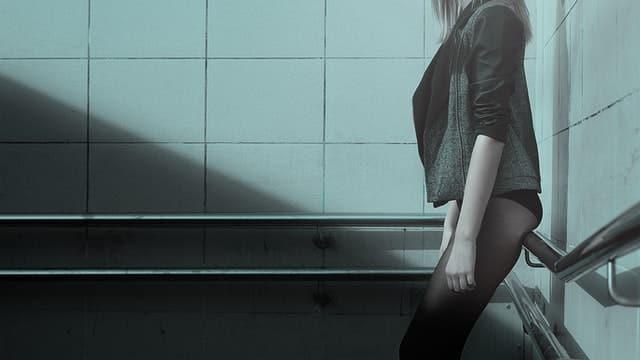 Mulher em pé encostada em corrimão usando meia calça, calcinha e moletom