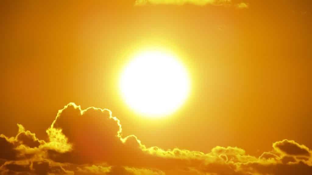 Sol visto ao entardecer, com nuvens a sua volta.