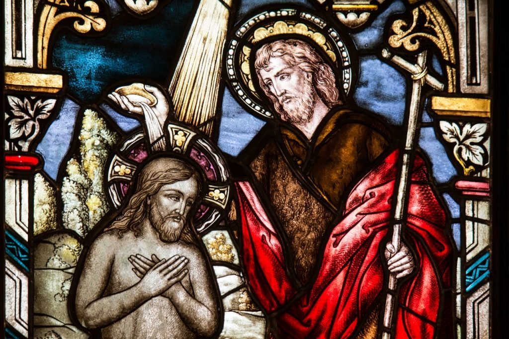 Arte em vidro em uma catedral, representando figuras cristãs.