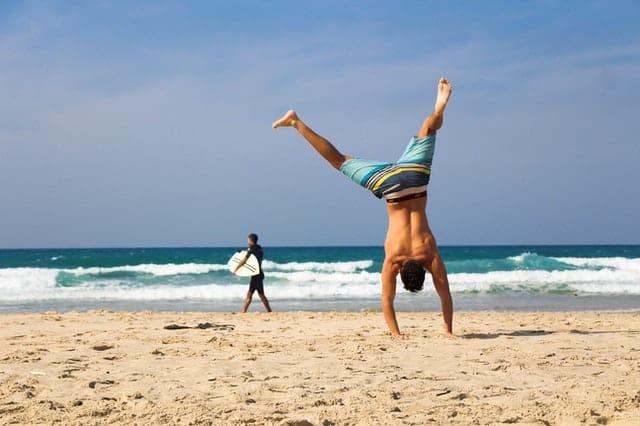 Homem fazendo estrela com mãos na areia e pernas para o alto na praia