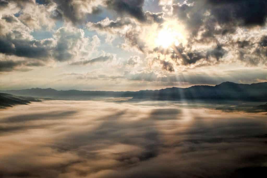 Sol iluminando nuvens e montanhas.