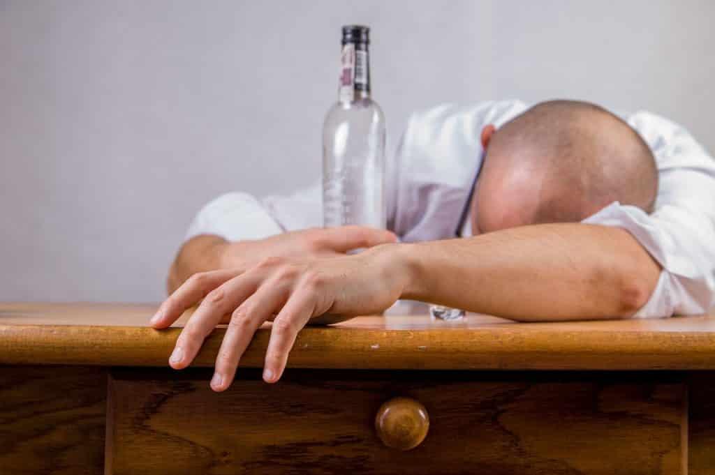 Homem debruçado sobre uma bancada abraçado a uma garrafa de bebida alcoólica.
