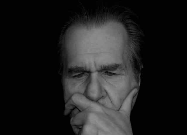 Homem com mão no rosto e expressão triste