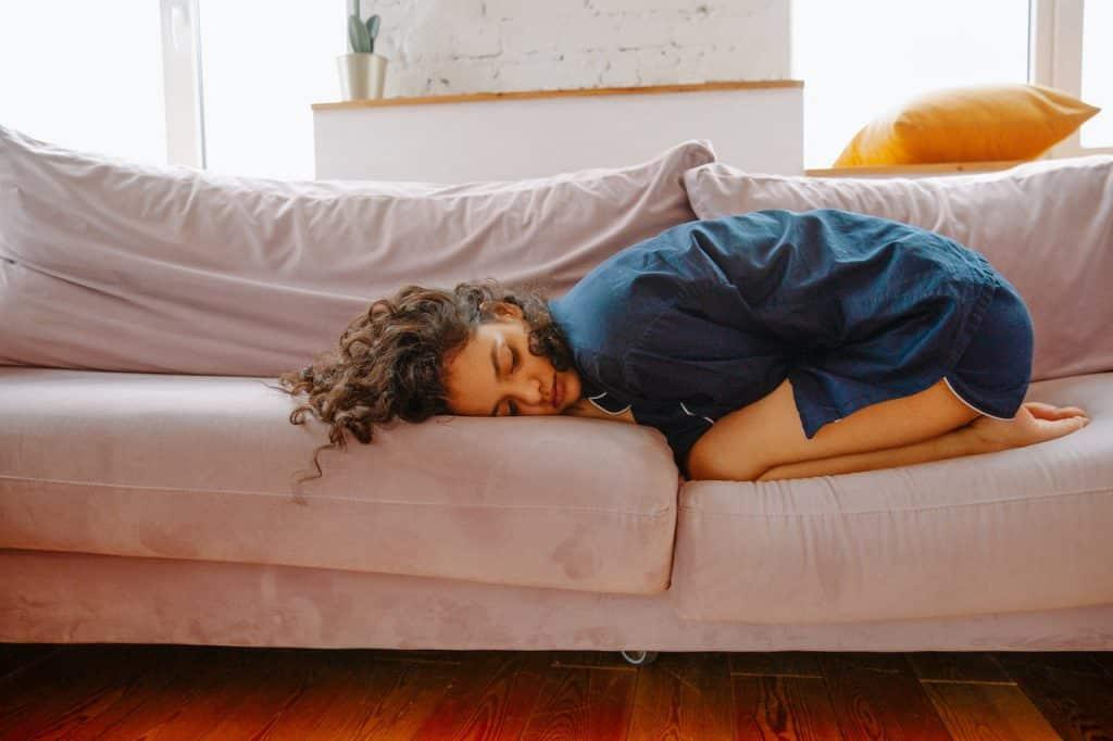 Mulher ajoelhada em um sofá, com o tronco flexionado para frente como se estivesse deitada para evitar a dor das cólicas menstruais.