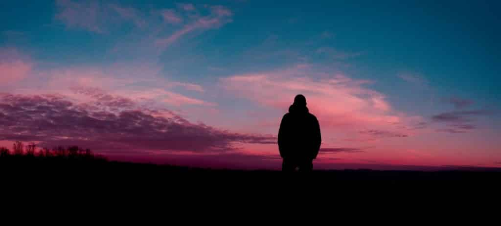 Silhueta de um homem olhando para a paisagem.