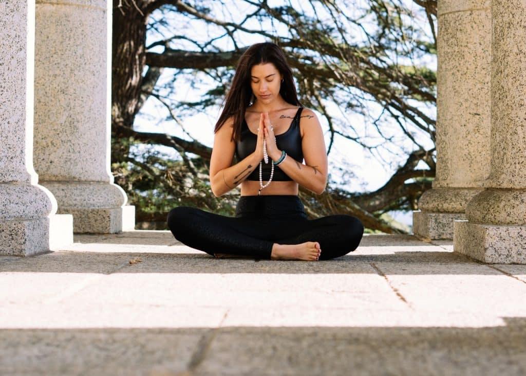 Mulher sentada em posição de meditação segurando um japamala.