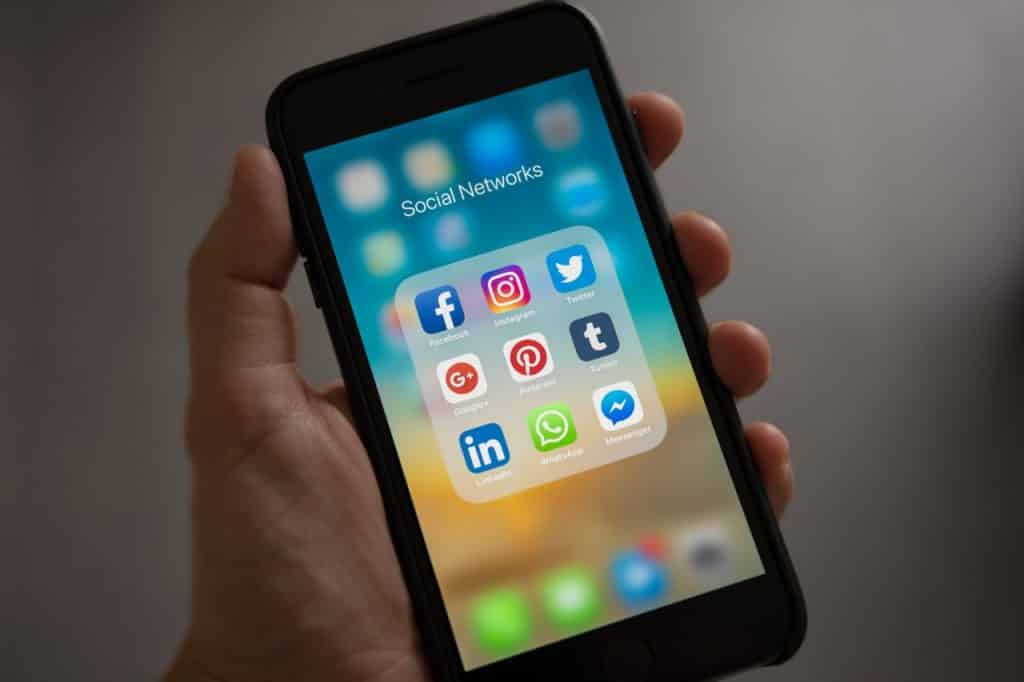 Mão segurando um telefone celular, que mostra uma pasta contendo aplicativos de mídias sociais.
