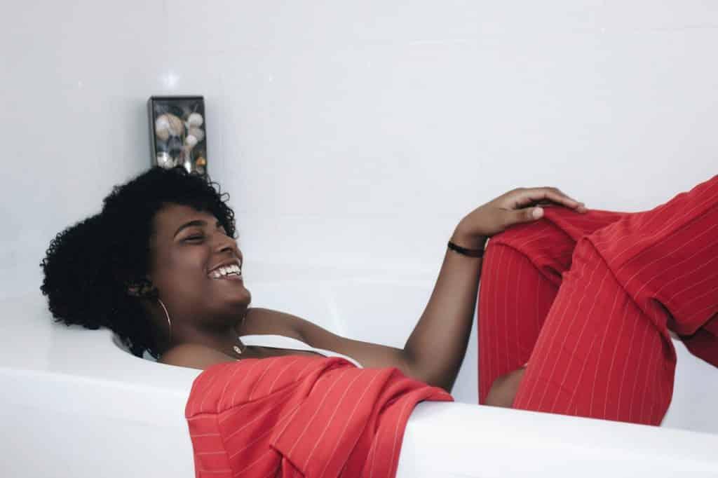 Mulher de roupas sociais deitada em uma banheira vazia, rindo.