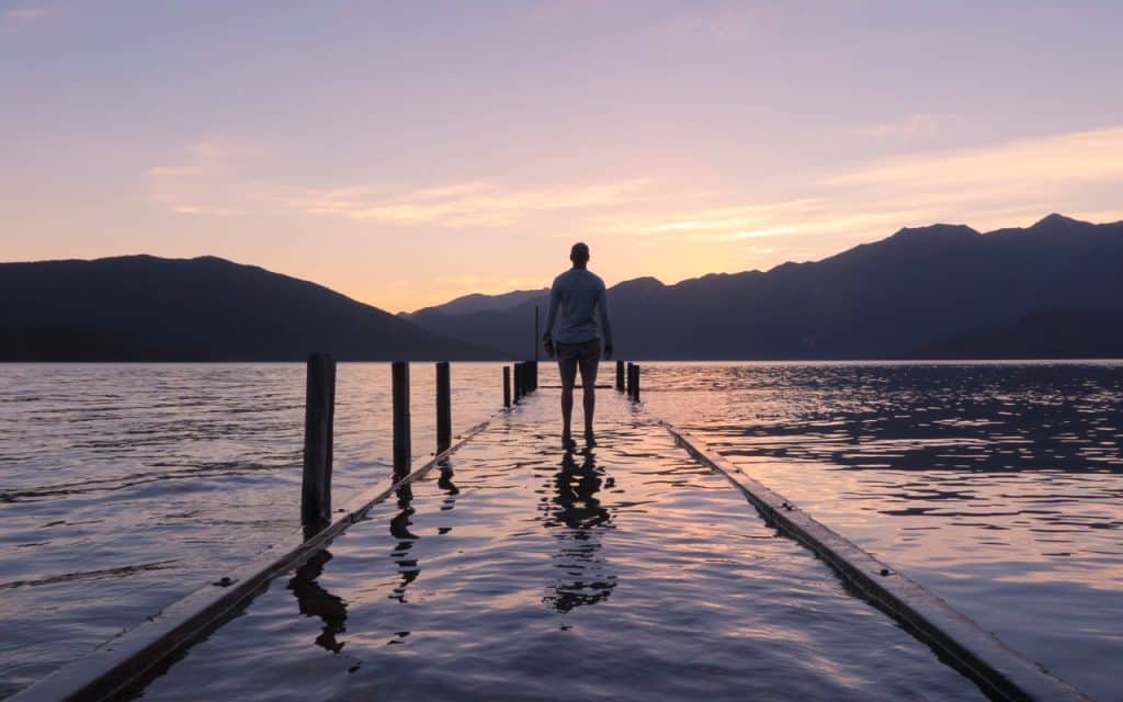 Homem em um pier de lago.