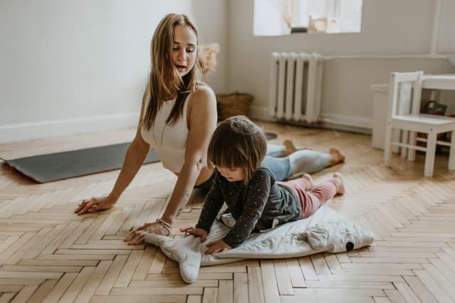 Mãe e filha fazendo exercícios no chão da sala