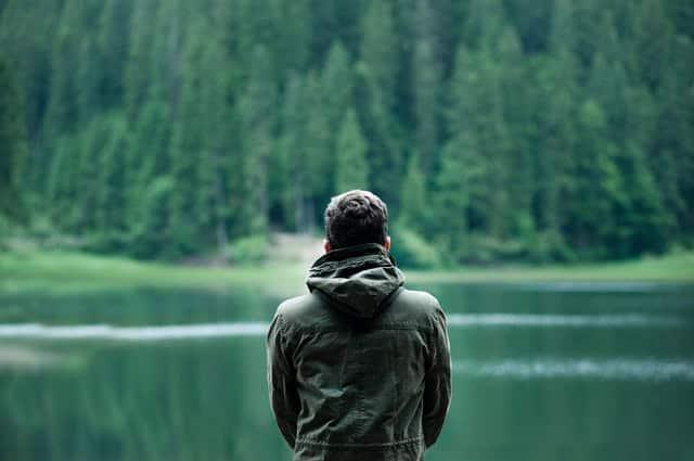 Homem em pé de costas com lago e árvores ao fundo