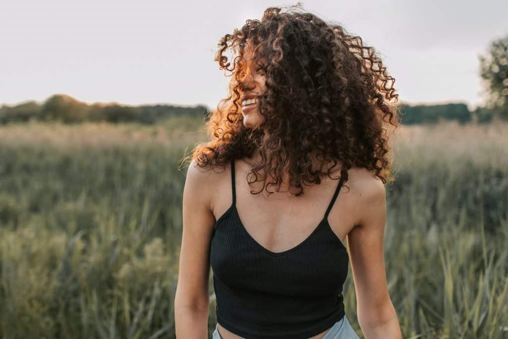 Mulher sorrindo com o cabelo no rosto em um campo de gramado