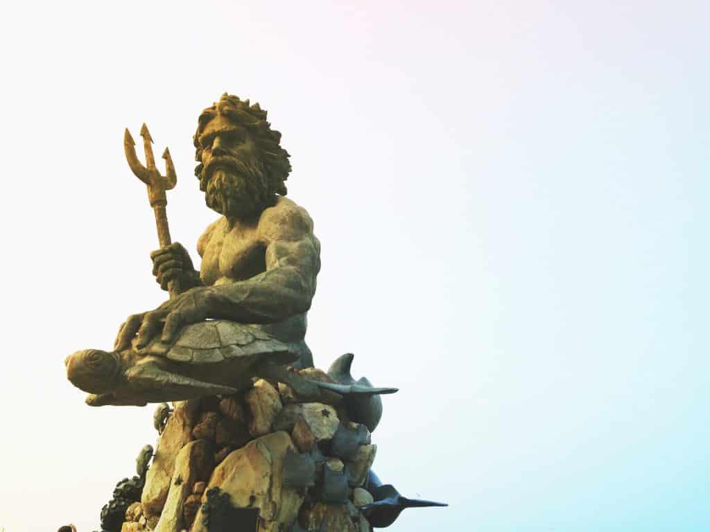 Estátua de poseidon como um homem barbudo segurando um tridente e apoiando uma das mãos em uma tartaruga.