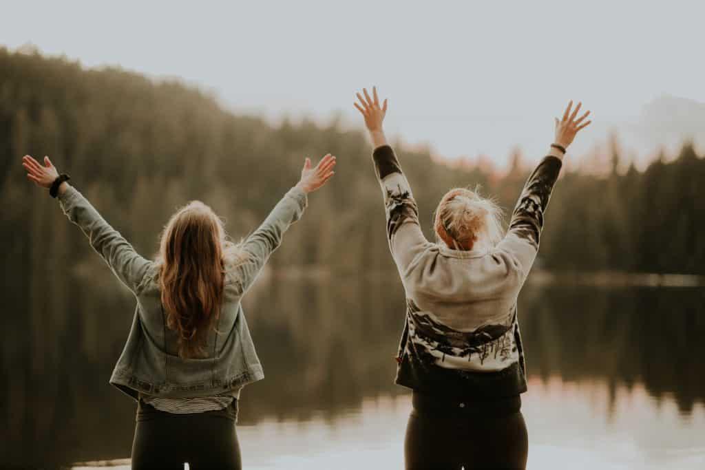 Duas mulheres brancas de costas com braços levantados e olhando para rio
