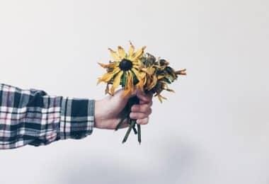 Homem segurando flores amarelas mortas