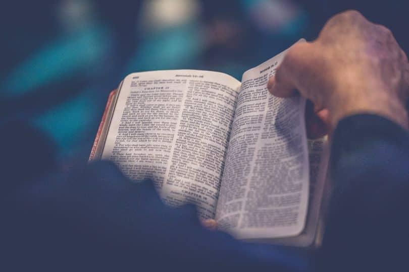 Homem segurando uma bíblia e foleando