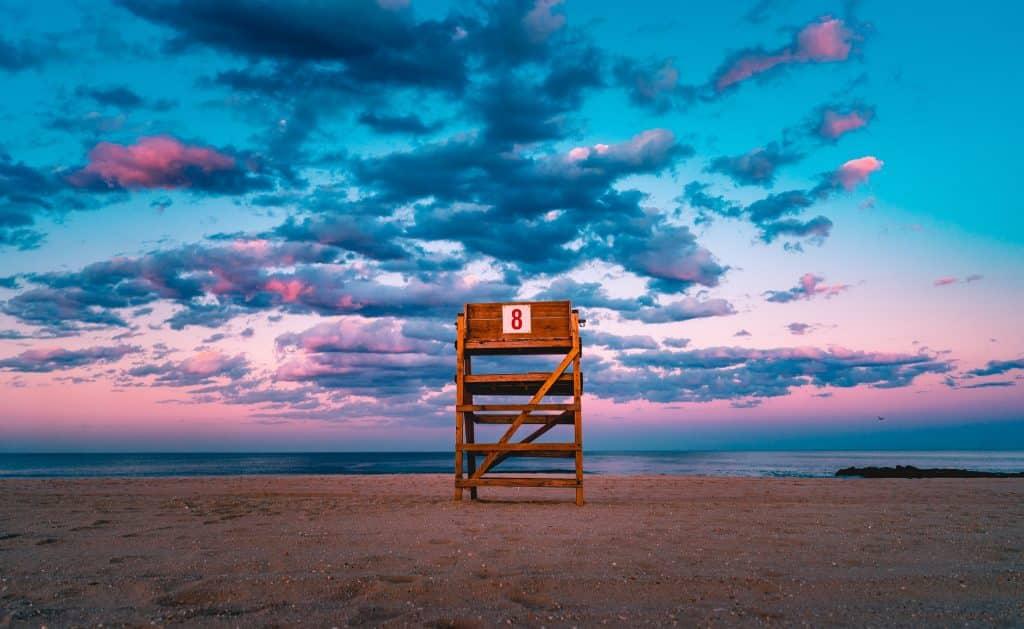 """Pedestal de madeira com o número """"8"""" na praia, pôr-do-sol ao fundo."""