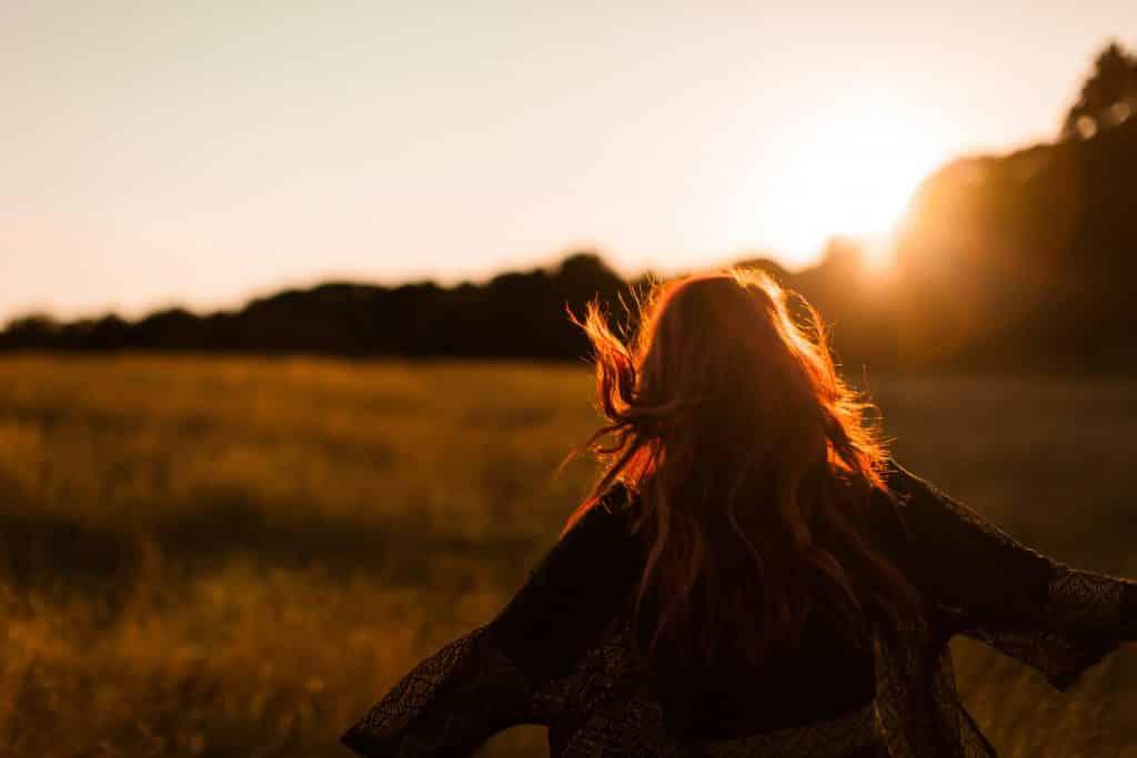 Mulher andando em um campo de flores ao pôr do sol com os braços abertos