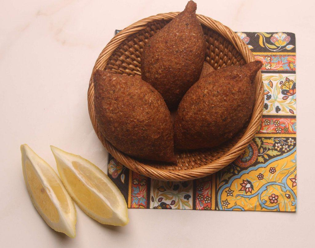 Imagem de três quibes vegetarianos prontos para serem servidos. Eles estão sobre uma cestinha de vime e ao lado um limão cortado em fatias.