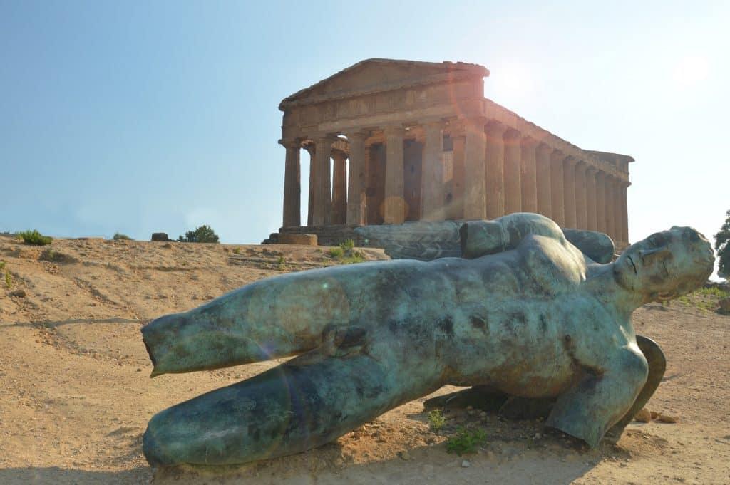 Estátua de Ícaro caída no chão, sem as pernas, braços e com as asas quebradas, em frente ao Partenon - um monumento cheio de pilares.