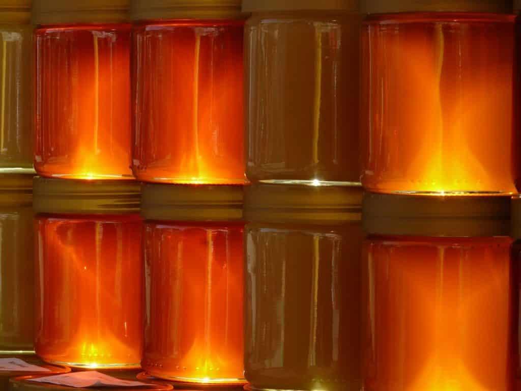 Potes de vidro com mel e própolis empilhados.