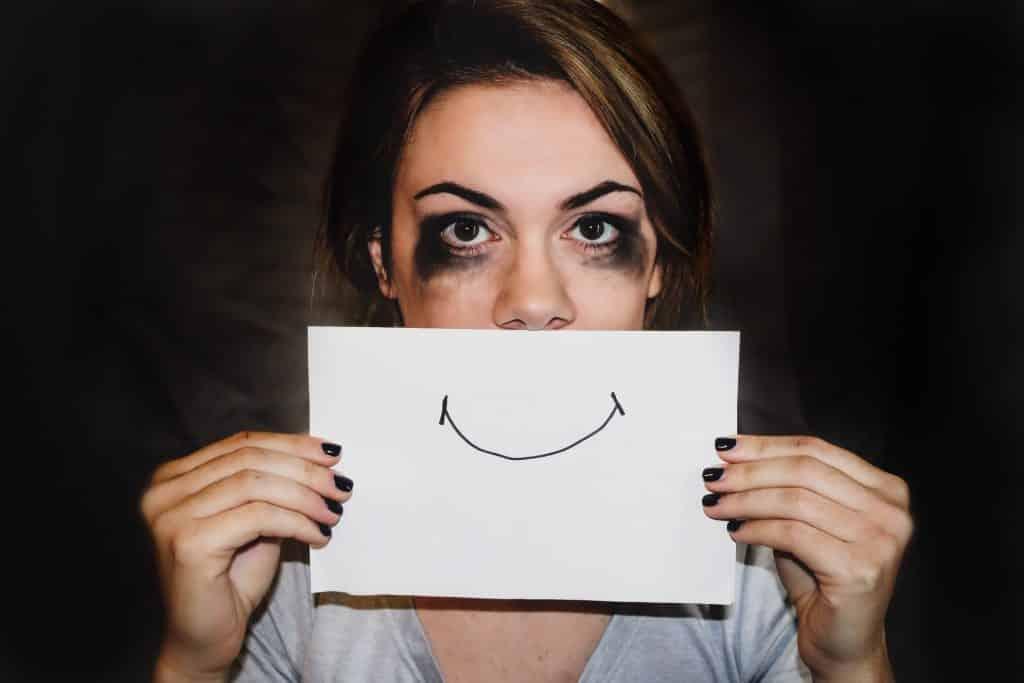 Mulher com os olhos borrados de maquiagem cobrindo a boca com uma folha de papel que possui um sorriso desenhado.