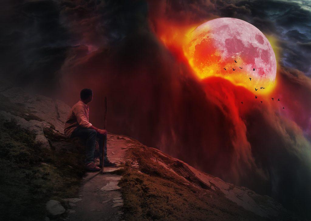 Homem no topo de uma montanha presenciando um fenômeno da Lua entre nuvens de fumaça e fogo.