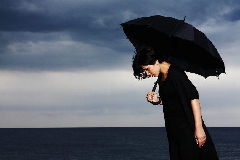 Imagem de um dia nublado na praia. Ao fundo uma mulher usando uma roupa preta e segurando um guarda chuva preto. Ela está com depressão.