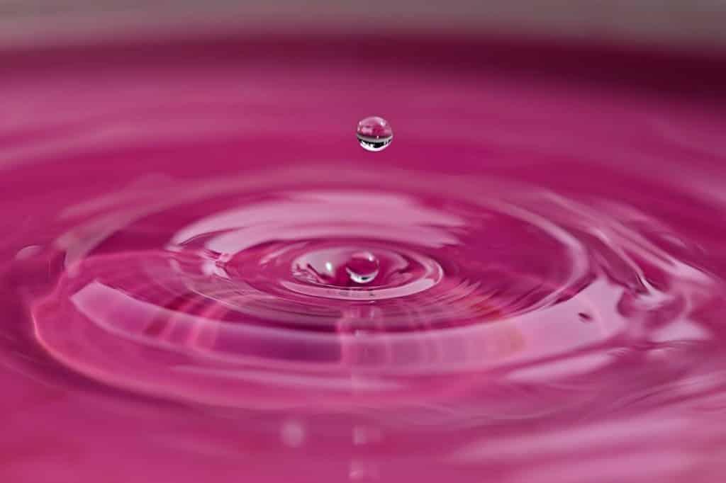 Imagem de uma gota d'água em um fundo cor de rosa.