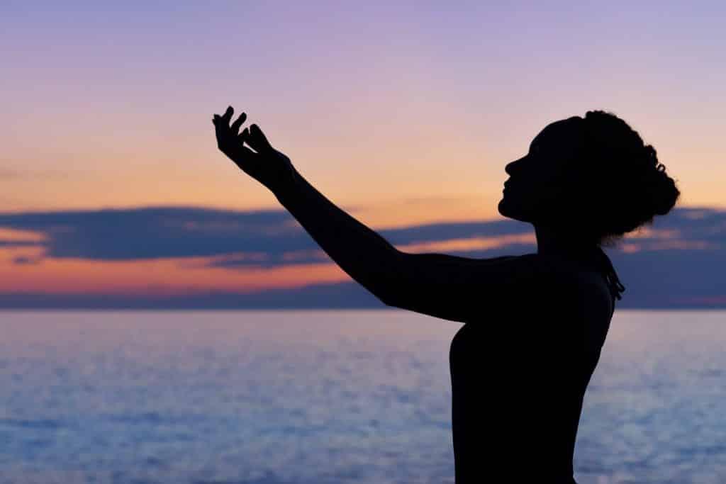 Silhueta de uma mulher vista de perfil em frente ao mar, ao pôr do sol.
