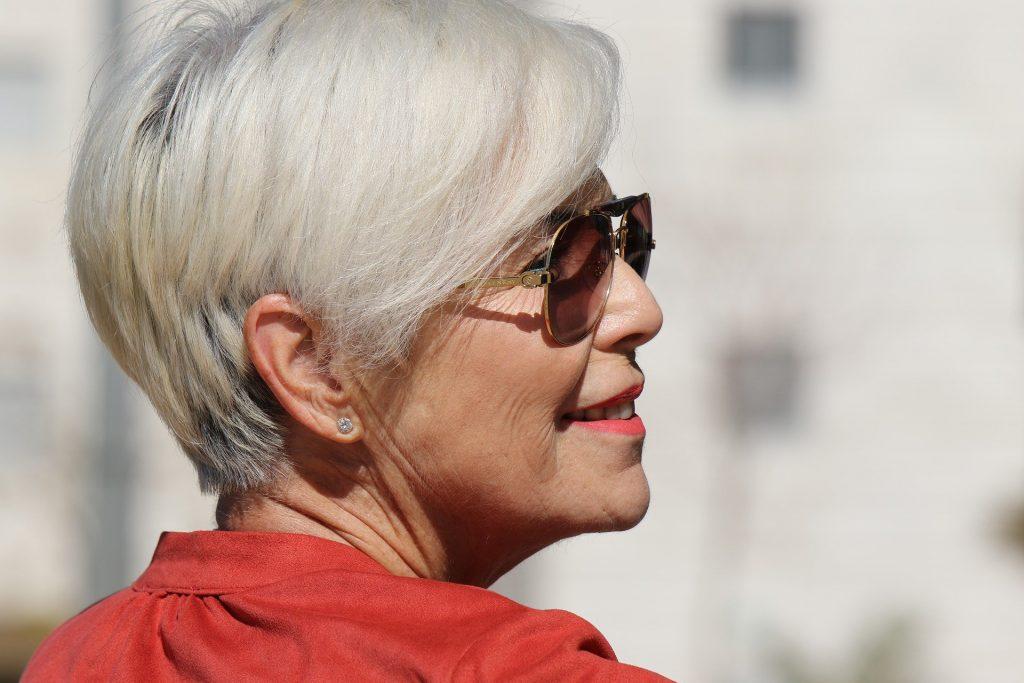 Imagem de uma mulher som lindos cabelos brancos e curtos. Ela usa óculos de sol e está bem feliz.