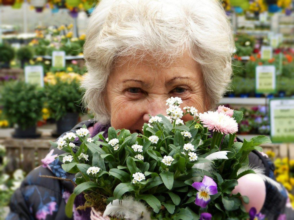 Imagem de uma senhora de cabelos brancos segurando um arranjo de flores em suas mãos.