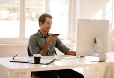 Homem branco sentado em frente a computador branco enquanto segura um celular.