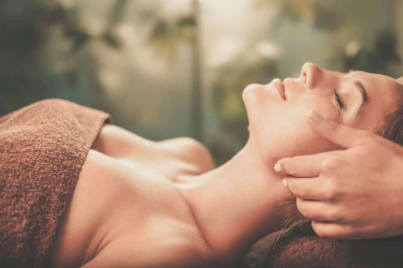 Mulher branca deitada com os olhos fechados, com uma mão ao lado da bochecha.