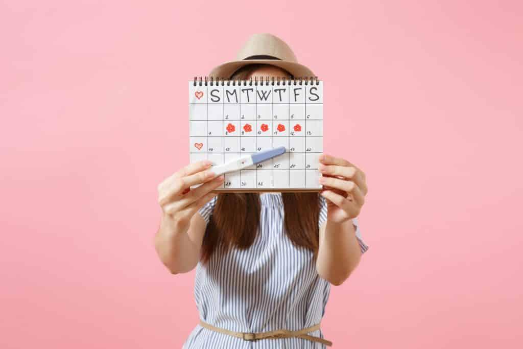 Mulher segurando calendário menstrual