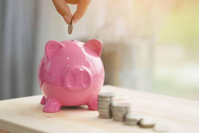 Pessoa depositando moedas em um cofre de porquinho sobre uma mesa de madeira.