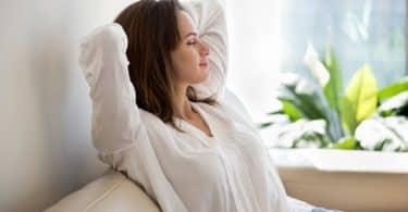 Mulher sentada em sofá com mãos atrás da cabeça e olhos fechados relaxando