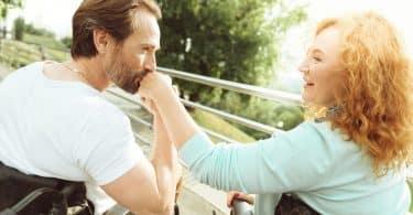 Homem e mulher brancos, ambos em cadeira de rodas, o homem beijando a mão da mulher.