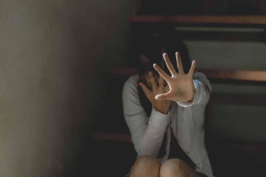 Mulher escondendo seu rosto sentada em uma escada e com a outra mão esticada par frente