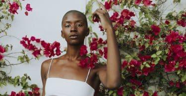 Mulher negra com top branco meio a uma árvore com flores vermelhas