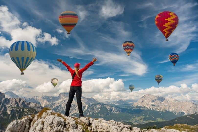Mulher de braços abertos no topo de uma montanha com balões ao fundo.