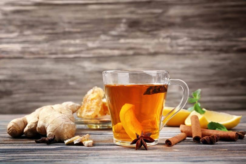 Xícara de vidro com líquido alaranjado, ao lado gengibre, canela em pau e fatias de limão.